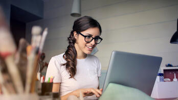 woman employee with glasses sitting at laptop