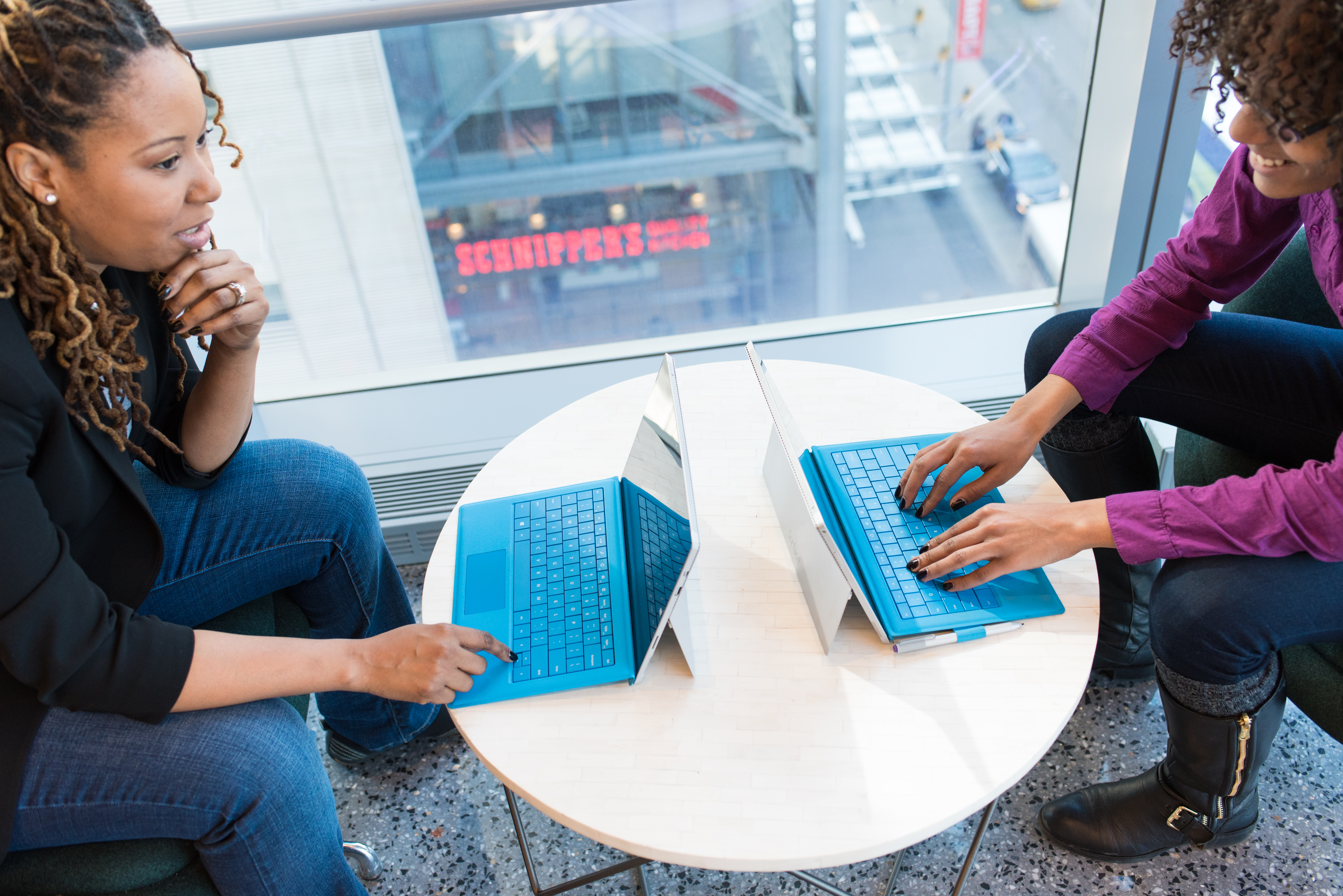 Canva - Two Women Browsing On Laptop Computers